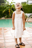 little Hispanic girl laughing standing by pool Stock Images