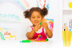 Little Hispanic looking girl play with plasticine. Beautiful Hispanic girl play with modeling clay in the class at kindergarten Royalty Free Stock Image