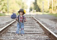 Little Hobo. Adorable little girl dressed as a hobo and walking on the railroad tracks stock photo