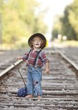 Little Hobo. Adorable little girl dressed as a hobo and walking the railroad tracks. Room for your text royalty free stock photo