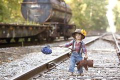 Little Hobo. Adorable toddler dressed as a hobo and holding her teddy on the railroad tracks. Room for your text royalty free stock photography