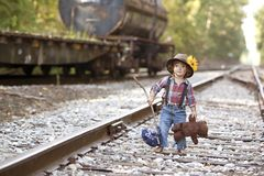 Little Hobo. Adorable toddler dressed as a hobo and holding her teddy on the railroad tracks. Room for your text stock photos