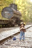 Little Hobo. Adorable toddler dressed as a hobo and hugging her teddy on the railroad tracks. Room for your text royalty free stock photos