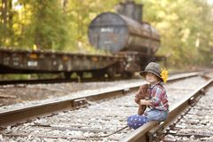 Little Hobo. Adorable toddler dressed as a hobo and hugging her teddy on the railroad tracks. Room for your text stock photos