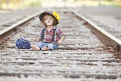 Little Hobo. Adorable toddler dressed as a hobo and sitting on the railroad tracks. Room for your text stock photography