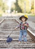 Little Hobo. Adorable toddler dressed as a hobo and standing on the railroad tracks. Room for your text royalty free stock image