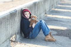 Little homeless boy holding a teddy bear Royalty Free Stock Images