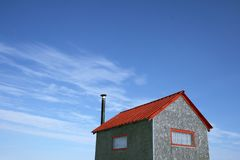 Little house and the blue sky. Little house with red roof and chimney and spacious blue sky (ice fishing hut stock photos