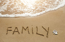 A little house and family written on the sand beach Royalty Free Stock Photo