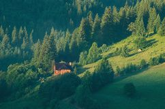 Little house on a green mountain slope Stock Image