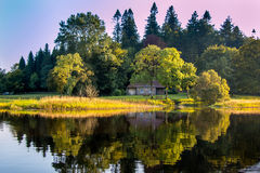 Little house by a lake and enchanted woods. Stock Photos