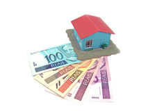 Little house and money. Little model house over a lot of brazilian real banknote royalty free stock images