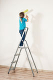 A little house-painter. A little girl painting the wall Stock Image