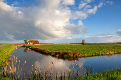 Little house, river, and white puffy clouds Royalty Free Stock Photos