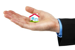 Little house symbol in hand. Man in a suit holding a little house in his palm Royalty Free Stock Photography