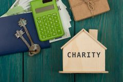 Little house with text & x22;Charity& x22;, keys, calculator, passport, gift box, money. On blue wooden background Stock Photography