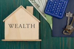 Little house with text & x22;Wealth& x22;, keys, calculator, passport, money. Little house with text & x22;Wealth& x22;, keys, calculator, passport Royalty Free Stock Photography