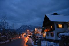 Little houses covered with snow and christmas lights at night. View from the road. Snowy mountains at the background. Bad Goisern, Hallstatt, Austria royalty free stock photos
