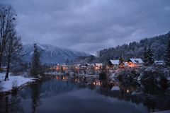 Little houses covered with snow and christmas lights. River view. at night. stock photo