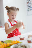 Little housewife engaged in baking muffins in the kitchen at home Royalty Free Stock Photography