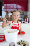Little housewife engaged in baking muffins in the kitchen at home Stock Photography