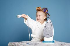 Little housewife with iron on blue background Royalty Free Stock Photos