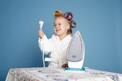 Little housewife with iron on blue background Stock Photo