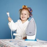 Little housewife with iron on blue background Stock Image
