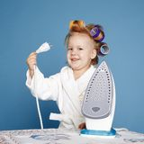 Little housewife with iron on blue background Royalty Free Stock Images