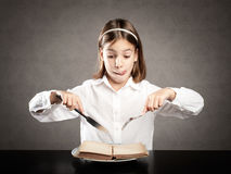 Little hungry girl in front of a book Stock Images