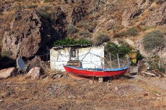 Little hut and a boat in front of hill Royalty Free Stock Photo