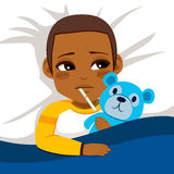 Little Ill Boy. Little African American boy ill in bed with thermometer and hugging blue teddy bear Stock Image