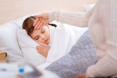 Little ill child sleeping peacefully in her bed. Sleeping child. Cute little ill girl sleeping while the caring loving mother touching her forehead royalty free stock photo