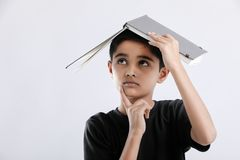 little Indian / Asian boy with book on head and thinking seriously stock photos