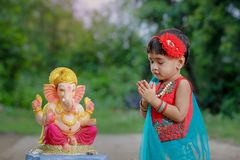 Little Indian girl child with lord ganesha and praying , Indian ganesh festival stock photos
