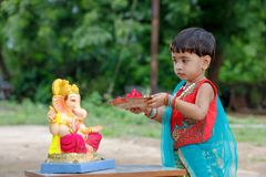 Little Indian girl child with lord ganesha and praying , Indian ganesh festival.  stock photo