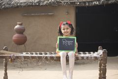 Rural Indian little girl holding slate at home stock photo