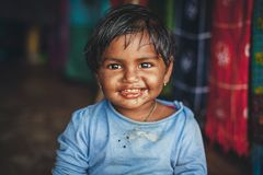 A little Indian girl looks at the camera and smiles at the photographer royalty free stock photography