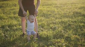 Little infant boy jumping on green grass with his father. Man in shorts holding tiny hands of son, hangling him up. Blond toddler enjoying, laughing and stock footage
