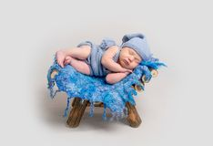Little infant boy sleeping on his side. With his hand under cheek. Baby lying on wooden crib covered with blue rug Stock Images