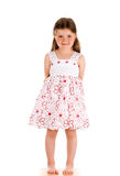 Little innocent girl standing. Little innocent girl on isolated background with hands behind her back Royalty Free Stock Image