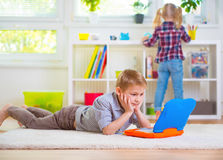 Little intelligent boy play with laptop at home Stock Image