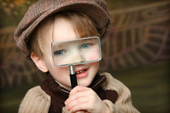 Little Investigator. Cute little Blue eyed boy with magnifying glass stock photos