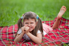 Little irritated girl preschooler lying on plaid Royalty Free Stock Photo