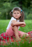 Little irritated girl sitting on plaid in grass Royalty Free Stock Photos