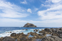 Little island. A small rocky island located not far from the coast, covered with lava stones of the island of Tenerife. Spain royalty free stock photography