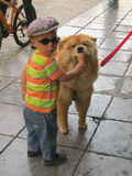Little Italian boy treats ice cream to dog Royalty Free Stock Photography
