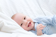 Little joyful baby resting on bed Royalty Free Stock Image