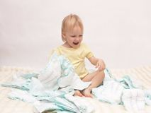 Little joyful girl playing with a pile of diapers on a white background, copy space, napkin. Little joyful girl playing with a pile of diapers on a white stock photos