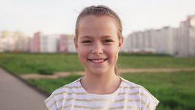 Little joyful girl smiling against urban lawn stock video